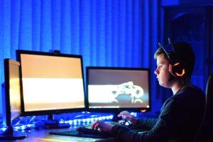 Junge an Computer, mehreren Bildschirmen
